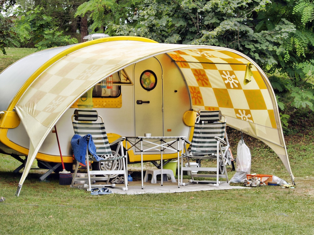 Caravan at camping site, table and empty chairs in front of