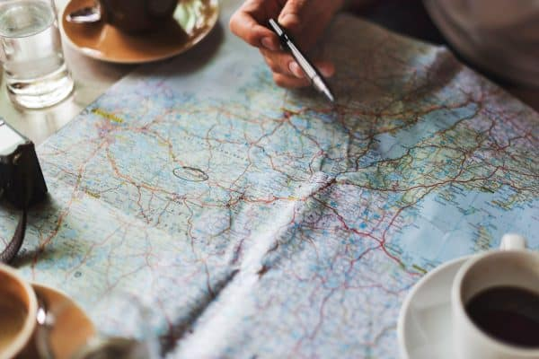 map with hand and pen pointing and coffee cup