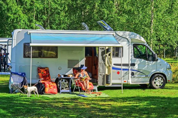 motorhome with woman reading book in swimsuit out front