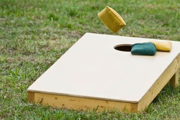 Cornhole board with bags and board being tossed