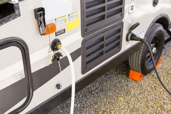 filling the water tank of a campervan in campground area