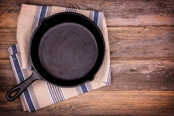 Empty cast iron skillet with tea towel, over old wood background. Retro style processing and space for your text. (Empty cast iron skillet with tea towel, over old wood background. Retro style processing and space for your text. , ASCII, 115 componen