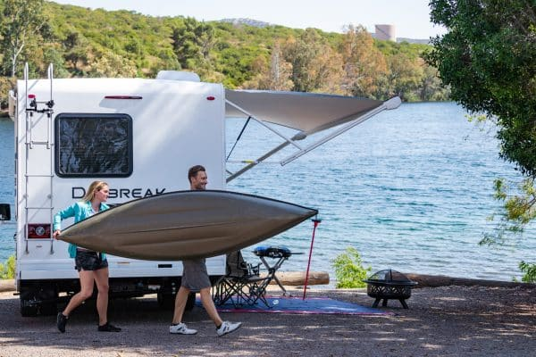 a couple camping in their RV with a Kayak by the water