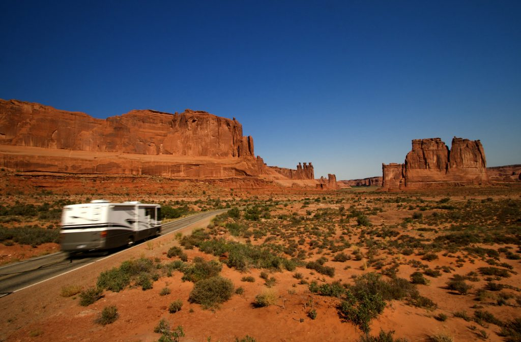 Summer vacation travelers tour through Arches National Park in Utah USA